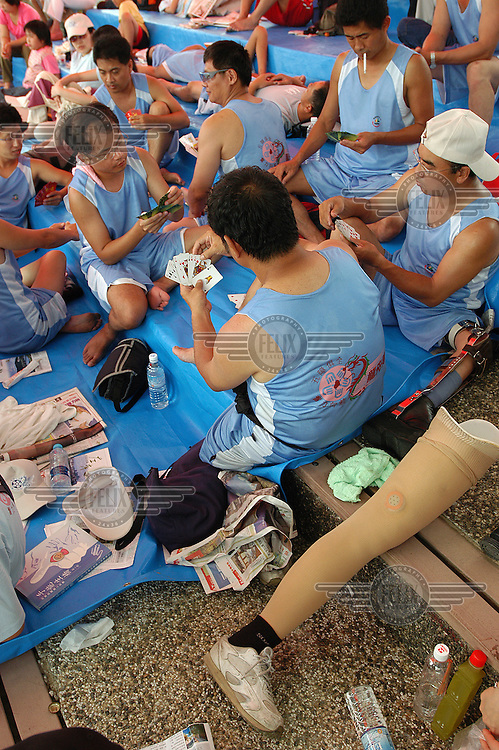 A team with disabilities play cards before taking part in the dragon boat races at Taipei's Dajia Riverside Park. Dragon boat races are held annually in Taipei around the end of May and officially herald the start of the summer season.