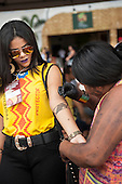 A Brazilian indigenous Kayapo woman paints a traditional design on the arm of a fashionable Brazilian woman at the International Indigenous Games in Brazil. 27th October 2015