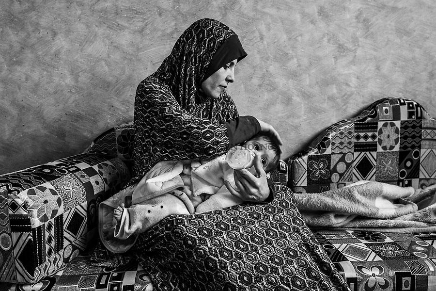 Gaza, Jabalia : Shadia Alsabagh nourrit son fils avec du lait en poudre. Avec le loyer qui est à 150$ par mois, son mari a du mal à payer le lait pour le nourrisson et doit emprunter de l'argent à sa mère. 07/02/16<br /> <br /> Gaza, Jabalia : Shadia Alsabagh feeds  her son  with powdered milk. With the rent is of 150$ a month, Shady has trouble paying the milk to the infant and must borrow money to his mother. 07/02/16