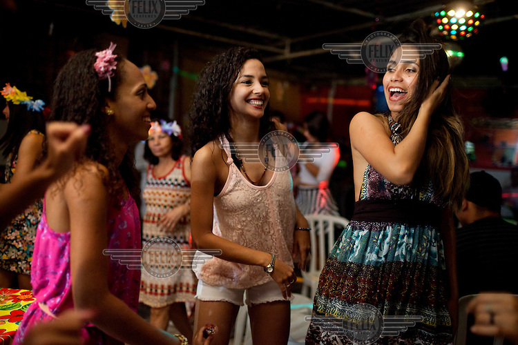 Amanda Oliveira, 18, right, dances with her friends at a birthday party, in Complexo da Mare. Amanda is a dance instructor and is learning English. so, she says: 'I'm going to get out of here one day.' The favela consists of a complex of 16 communities, in the north zone of Rio de Janeiro. It is the largest complex of favelas, housing 130,000 residents. It is targeted for pacification as the city prepares for the 2014 World Cup and the 2016 Olympics. Four factions run the complex, three drug gangs and the militia. The rival gangs fight for control of the drug trade. Although crime is low in the favelas by rule of law enforced by the gangs, cross-fire shootings and gang violence is often high. Neighborhood associations are an integral part of community development within Mare, making up for a lack of government assistance.