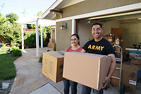 Young military couple on moving day with professional movers and van in background. Man wears ARMY t-shirt. Model released and DOD compliant for advertising.