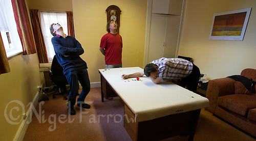 24 OCT 2013 - CAMBRIDGE, GBR - Challenger Patrick Barrie (GBR) (right) of Great Britain rues a missed pot watched by title holder Larry Kahn (USA) (centre) of the USA and umpire Matt Fayers (left) during tiddlywinks World Singles 67 in Barrie's office at Emmanuel College, Cambridge, Great Britain. Barrie who took up the sport as an undergraduate at the university in 1984 now lectures in Chemical Engineering there (PHOTO COPYRIGHT © 2013 NIGEL FARROW, ALL RIGHTS RESERVED)