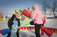Dominick Miserandino helps his daughter Caterina as she plays jousting with her mother Margherita at the Quebec Winter Carnival (Carnaval de Quebec) in Quebec city, February 3, 2010. With close to one million participants, it has grown to become the third largest winter celebration in the world.