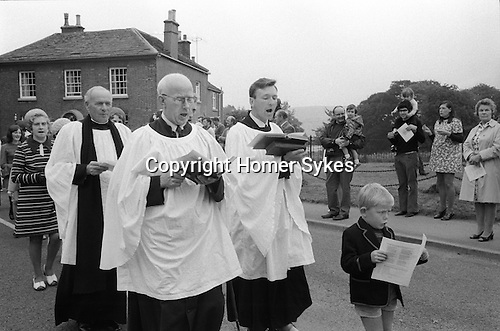 Eyam Memorial Service. Eyam, Derbyshire England 1973. Last Sunday in August.<br /> <br /> In August 1665 the bubonic plague, known as the Black Death arrived at the house of the village tailor George Viccars, believed probably to be via an infected parcel of damp cloth delivered to his workshop from London. On 7th September, George Viccars, was the first plague victim in Eyam. On the advise of the rector William Mompesson and the previous incumbent Thomas Stanley, villagers imposed a strict curfew on themselves, and lived within the boundary of the village. To minimise cross infection, food and other supplies were left at both boundary stones, or at Mompesson's Well, some distance from the village. The Earl of Devonshire, who lived nearby at Chatsworth House, donated food and medical supplies during the fourteen month self-imposed quarantine, which did, successfully contain the spread of disease. Approximately 260 members of the community died out of a population of 350. During this time members of families buried there own dead, and church services were held outdoors at nearby Cucklet Delf. The self sacrifice of the villagers prevented the plague from,  no cases of the disease were reported outside of the village.  <br /> <br /> Since 1905 Plague Sunday has been celebrated to commemorate the sacrifice the villagers made.  A procession led by the village rector walks from the Parish Church of St Lawrence to Cucklet Delf where a memorial service of commemoration is held  and the plague hymn is sung.