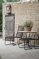 The sand coloured walls of a former stables provide a rich yet neutral background for simple garden furnishings and native plants. Iron and terracotta details provide textured relief against the simple earth and stone coloured backdrop.