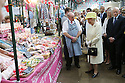 Stall holder Jim Moore makes Britain's Queen Elizabeth II laugh as she tours St.Georges Market in Belfast, Tuesday June 24th, 2014. The Queen is on a 3 day tour of Northern Ireland. Photo/Paul McErlane