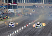 Jul. 19, 2014; Morrison, CO, USA; NHRA funny car driver John Force (right) races alongside Robert Hight during qualifying for the Mile High Nationals at Bandimere Speedway. Mandatory Credit: Mark J. Rebilas-