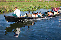 Myanmar, Burma.  School Children Riding  Home after School, Inle Lake, Shan State.  The school boat rather than the school bus is the mode of transportation for these children living in the villages of Inle Lake.
