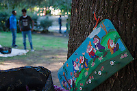 Italy. Lombardy Region. Como. Homeless african migrants living in the park below the San Giovanni railway station. A painting of the Seven Dwarfs is fixed on a tree trunck. The painting is normally used in a child's room to hang clothes. The Seven Dwarfs are a group of seven dwarfs that live in a tiny cottage and work in the nearby mines. The original Snow White story, written by the Brothers Grimm, did not feature names to any of the dwarfs. 11.08.2016 © 2016 Didier Ruef