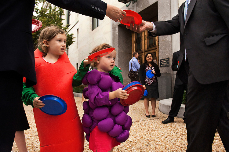 "WASHINGTON, DC - June 16: Bunch-of-grapes Maden Murray, 4, and her sister, carrot Davan Murray - who just turned 6 - pass out plates, with a message attached urging timely passage of a school nutrition bill, to Senate staffers arriving for work at the Dirksen Senate Office Building. The Center for Science in the Public Interest organized the push to get the ""Healthy, Hunger-Free Kids Act"" (S. 3307) to the Senate floor this month. The message glued to each plate, which were red and blue respectively, was headlined, ""Congress has a lot on its plate, but it needs to address what's on kids' plates - now!"" (Photo by Scott J. Ferrell/Congressional Quarterly)"
