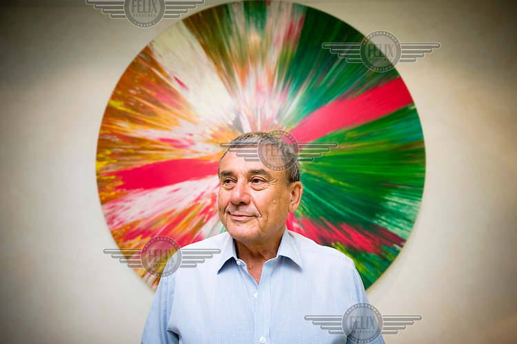 Billionaire hotel owner Sol Kerzner in his luxury home in Holland Park, West London. Behind him is a Damien Hirst spin-painting..
