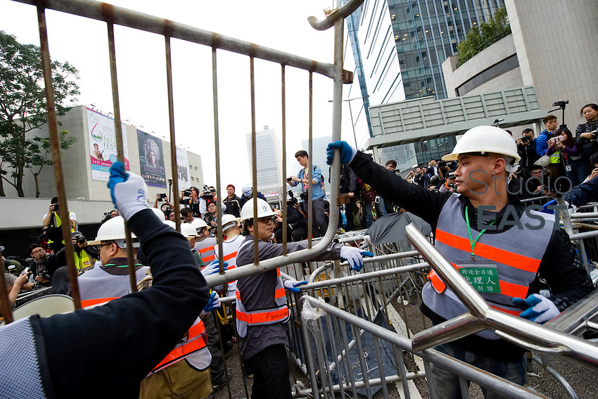 HONG KONG - DECEMBER 11: Workers take down barricades put up by pro-democracy protesters under the supervision of bailiffs following a court injuction December 11, 2014 in Hong Kong. (Photo by Lucas Schifres/Getty Images)