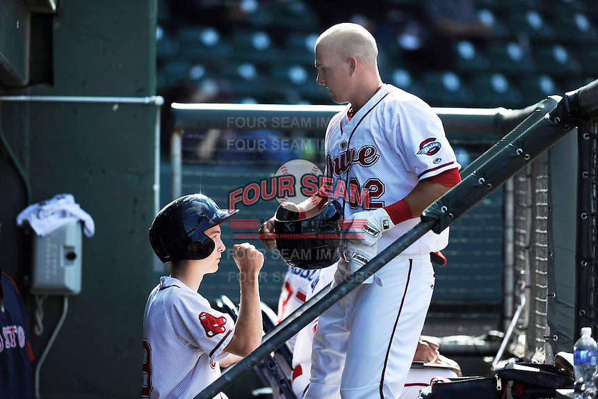 Third baseman Kevin Mager (32) of the Greenville Drive is greeted only by the bat boy, getting the silent treatment from teammates after hitting his first professional home run in a game against the Delmarva Shorebirds on Monday, April 29, 2013, at Fluor Field at the West End in Greenville, South Carolina. After a few seconds they congratulated him. Delmarva won, 6-5 in game one of a doubleheader. (Tom Priddy/Four Seam Images)