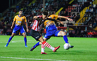 Lincoln City's Kellan Gordon crosses the ball despite the attentions of Mansfield Town's Lewis Gibbens<br /> <br /> Photographer Chris Vaughan/CameraSport<br /> <br /> The EFL Checkatrade Trophy Group H - Lincoln City v Mansfield Town - Tuesday September 4th 2018 - Sincil Bank - Lincoln<br />  <br /> World Copyright © 2018 CameraSport. All rights reserved. 43 Linden Ave. Countesthorpe. Leicester. England. LE8 5PG - Tel: +44 (0) 116 277 4147 - admin@camerasport.com - www.camerasport.com
