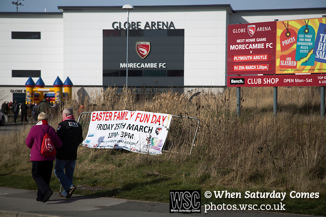 Morecambe 0 Plymouth Argyle 2, 25/03/2016. Globe Arena, League 2. Two fans arriving at the Globe Arena before Morecambe hosted Plymouth Argyle in a League 2 fixture. The stadium was opened in 2010 and replaced Morecambe's traditional home of Christie Park which had been their home since 1921, the year after their foundation. Plymouth won this fixture by 2-0 watched by 2,081 spectators, in a game delayed by 30 minutes due to traffic congestion affecting travelling Argyle fans.  Photo by Colin McPherson.