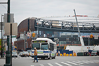 Traffic and pedestrians at the intersection of Flatbush and Atlantic Avenues pass construction on the Barclays Center in Brooklyn in New York Thursday, April 26, 2012. The new stadium for the Nets basketball team is scheduled to open in September 2012.  NYC Mayor Michael Bloomberg along with executives from the builder Forest City Ratner Companies announced that the new arena will fill positions for 2000 jobseekers and will soon hold hiring fairs in conjunction with the city's Workforce1 job centers. (© Richard B. Levine)