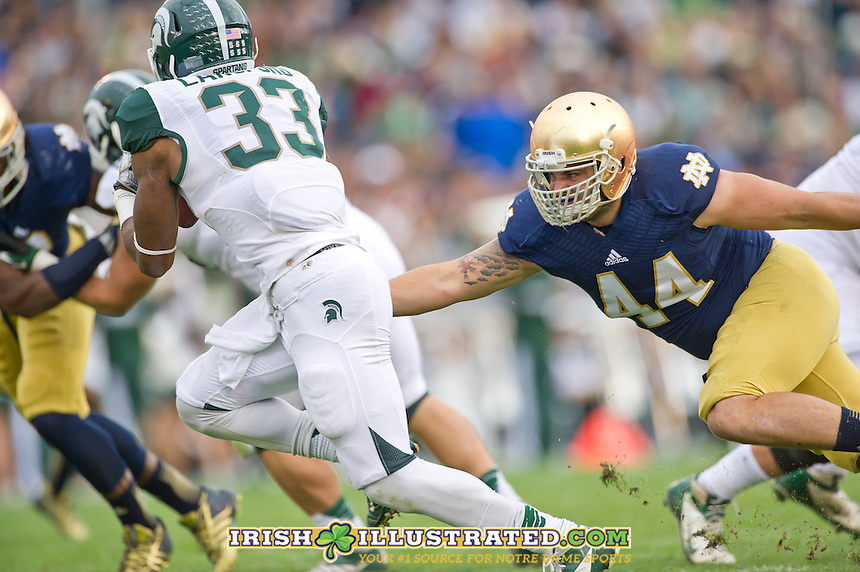 Linebacker Carlo Calabrese (44) chases down Michigan State Spartans running back Jeremy Langford (33).