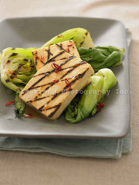 A dish of grilled tofu steaks and halved baby bok choy.