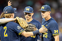 Michigan Wolverines first baseman Jimmy Kerr (15) talks with his teamamtes in between innings during Game 6 of the NCAA College World Series against the Florida State Seminoles on June 17, 2019 at TD Ameritrade Park in Omaha, Nebraska. Michigan defeated Florida State 2-0. (Andrew Woolley/Four Seam Images)