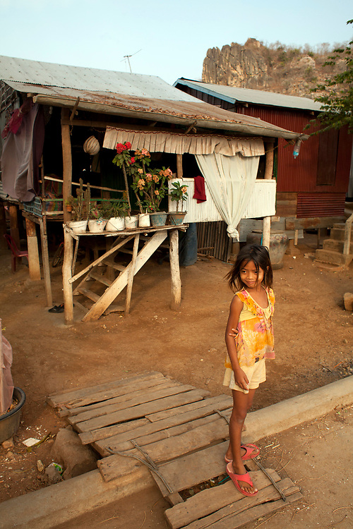 A young girl stands outside her house in a small village near Battambang, Cambodia. <br /> <br /> Photos &copy; Dennis Drenner 2013.