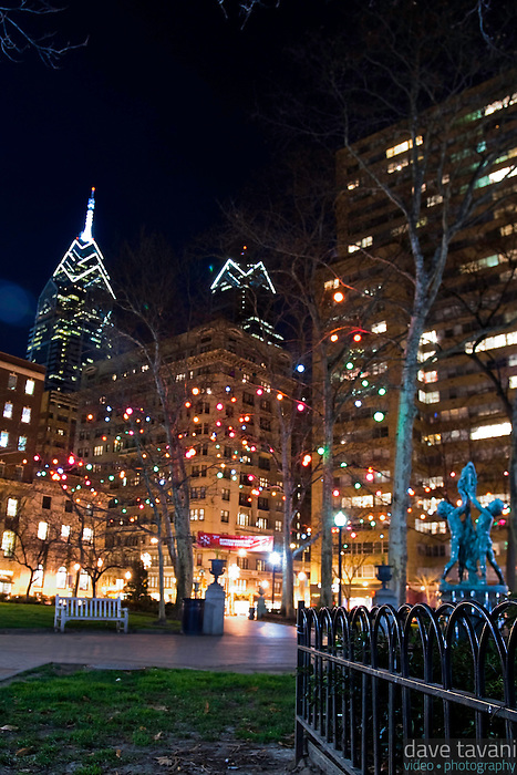 Holiday lights adorn Rittenhouse Square beneath the Philadelphia skyline.