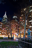 Holiday lights adorn Rittenhouse Square beneath the Philadelphia skyline.