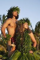 Male (kane) and female (wahine) hula dancers deep in thought, wearing palapalai fern head lei.