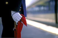 A station controller wears white gloves and holding a flag on the Shinkansen platform of Tokyo, Japan. Shinkansen literally means new trunk line, is a network of high-speed railway lines in Japan operated by four Japan Railways Group companies.    <br />