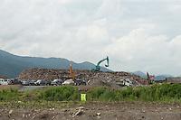 Construction vehicles create a pile of debris during reconstruction efforts following the 311 Tohoku Tsunami in Ofunato, Japan  © LAN