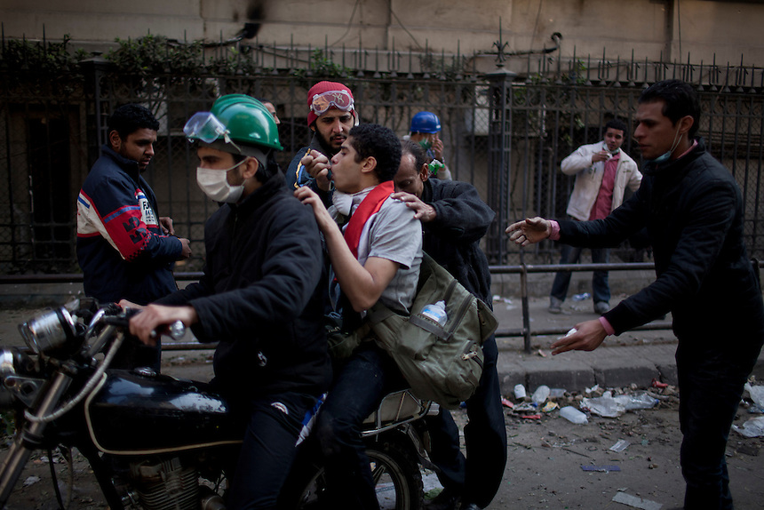 An Egyptian protester overcome by tear gas is ferried away from the front line during clashes near Cairo's Tahrir Square, November 22, 2011.  Photo: Ed Giles.