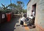 Edith Ncube had polio as a child and today uses a wheelchair in Bulawayo, Zimbabwe. Her wheelchair was provided by the Jairos Jiri Association with support from CBM-US. In this image she is helped out of her house by Deborah Sibanda (left), a community rehabilitation worker for Jairos Jiri, and her son Delight.