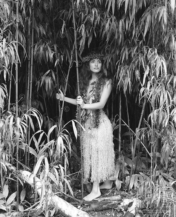 Young Hawaiian girl in bamboo forest, Kohala Mountains wearing maile lei, grass skirt and lei poo (head lei).