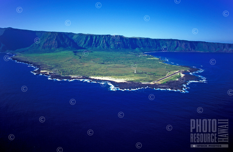 Aerial view of the northeast side of the Kalaupapa peninsula, showing the lighthouse in the center, and the topside of Molokai in the background.