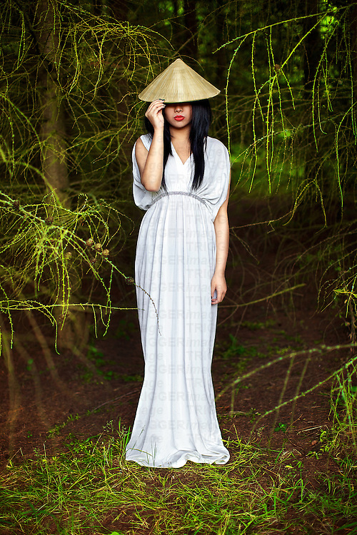 A young oriental woman in traditional Vietnamese hat and flowing white dress, posing in vibrant green fir trees.