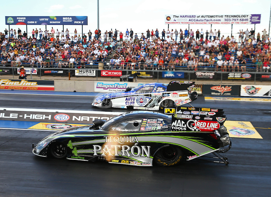 Jul. 19, 2013; Morrison, CO, USA: NHRA funny car driver Alexis DeJoria (near lane) races alongside Robert Hight during qualifying for the Mile High Nationals at Bandimere Speedway. Mandatory Credit: Mark J. Rebilas-