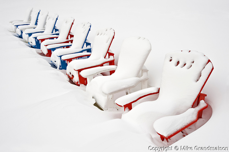 Muskoka chairs covered in snow in winter<br />