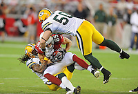 Aug. 28, 2009; Glendale, AZ, USA; Arizona Cardinals wide receiver (85) Jerheme Urban is hit by Green Bay Packers cornerback (31) Al Harris and linebacker (50) A.J. Hawk in the first quarter during a preseason game at University of Phoenix Stadium. Mandatory Credit: Mark J. Rebilas-