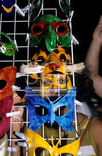 Rio de Janeiro, Brazil. Street carnival; vendor selling colourful carnival masks displayed on a wire mesh with clothes pegs.