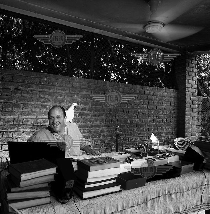 Writer and historian William Dalrymple, a cockatoo perched on his shoulder, in his writing 'shed' at the bottom of his garden in Dehli....