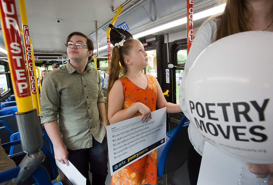 Breanna Kelley a 3rd grader at Riverview Elementary (C) and Cole Beckman (L) 9th grade at Ft. Vancouver High School look at poems they wrote displayed in a bus in downtown Vancouver Sunday July 3, 2016. The C-Trans program, Poetry Moves features poems written by school kids, displayed in busses. (Photo by Natalie Behring/ The Columbian)