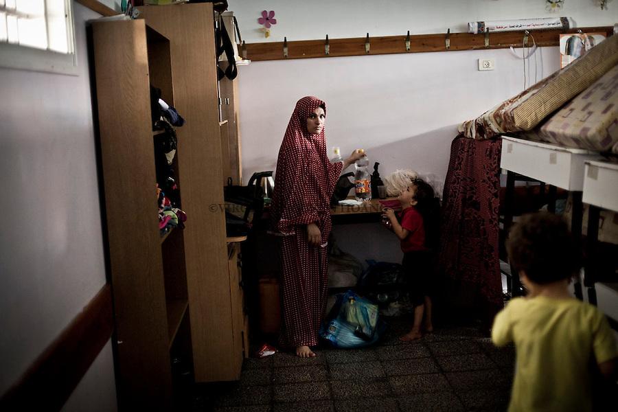 GAZA: La plupart des r&eacute;fugi&eacute;s de  l'&eacute;cole de la Sainte Famille sont de Beit Hanoun, Shujayea et Betlaya pr&egrave;s de la fronti&egrave;re isra&eacute;lienne. Ici, une femme r&eacute;fugi&eacute;e dans une salle de classe o&ugrave; elle vit. 1st Ao&ucirc;t.<br /> <br /> GAZA: Most of the people refugee in the Holy Family School are from Beit Hanoun, Shujayea and Betlaya near the Israeli border.  Here a refugee woman is hanging around a classroom where she lives. 1st August.
