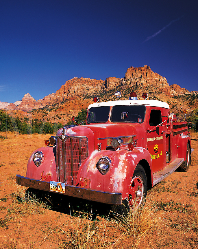 Old-style red fire engine parked on scrubland at the entrance to Zion Canyon, Utah, US