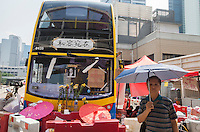 A man holds an umbrella next to an abandoned bus adorned with pro-democracy slogans and a mock shrine for Hong Kong Chief Executive Leung Chun-ying, on day three of the mass civil disobedience campaign Occupy Central, Hong Kong, China, 30 September 2014.