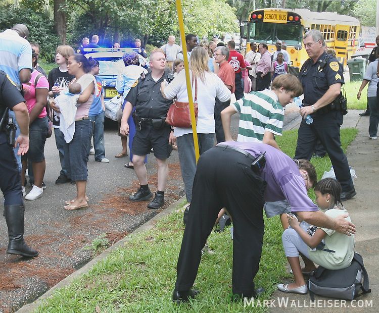 Cobb middle School principal Bob McDaris, right, comforts one of his students Kanyra Johnson, 11 years-old, as parents, children, school officials and emergency workers work to make sure each of the 42 children from Cobb Middle School aboard the bus are accounted for after a Leon County School bus collided with a pick up truck at the intersection of 7th Ave and Mitchell St. in Tallahassee, Florida  September 14, 2007.  (Mark Wallheiser/TallahasseeStock.com)