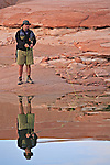 A fly fisherman fly fishes in mirrorlike waters in Padre Bay along Lake Powell's rocky shoreline