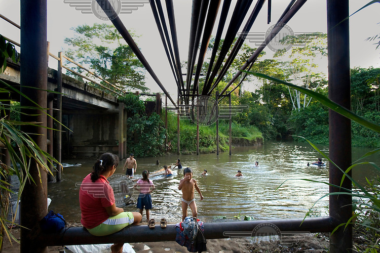 Children swim and play in the water, below where a large number of oil pipes cross a river. A class action lawsuit was brought against US multinational oil giant Texaco (acquired by Chevron in 2001) by more than 30,000 Ecuadorians. The case has been in the Ecuadorian courts since 2003 and relates to the dumping of billions of gallons of toxic materials into unlined pits and Amazonian rivers. In February 2011 the court ruled that Chevron should pay a fine totalling 9.5 billion USD. However, Chevron has stated that the ruling is 'illegitimate and unenforceable' and has started numerous counter proceedings in US courts. There is some doubt as to whether it will be possible to force Texaco to pay the fine.