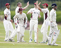 Joel Hughes (2nd L - no cap) of North Middlesex is congratulated after taking the wicket of Rob Jones (R) during the ECB Middlesex Premier League game between North Middlesex and Hampstead at Park Road, Crouch End on Saturday May 17, 2014