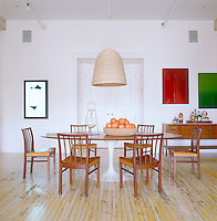 In the dining room an animation by Julian Opie and a pair of framed prints by James Welling, part of a large contemporary collection, hang on the white limewashed  wall adjacent to a vintage Saarinen table and chairs by Jacob Kjaer