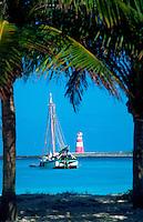 Fishing boat and lighthouse framed by palm trees. Nassau, Bahamas.