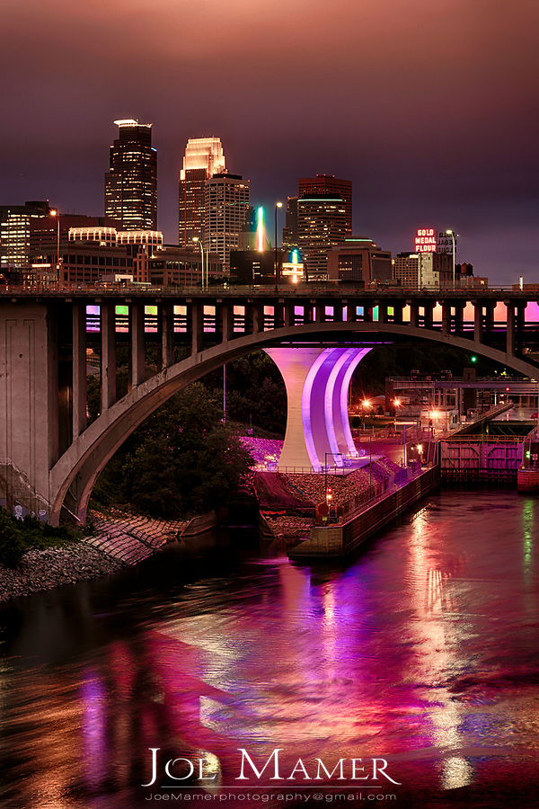 Minneapolis skyline with the interstate 35w bridge lit in multiple colors.